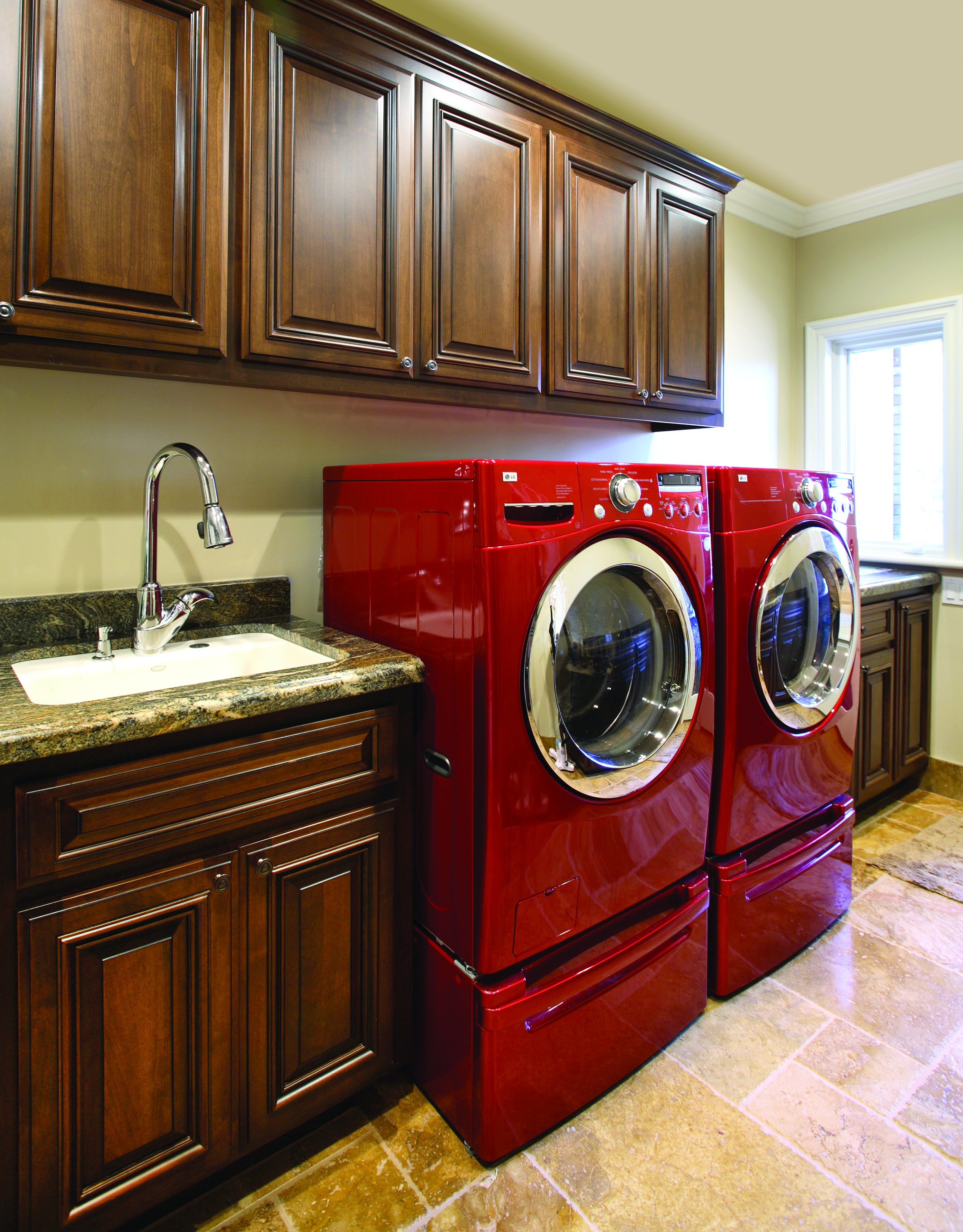 Traditional Stained Laundry Room Cabinets with a Beautiful Granite Countertop and Red, LG Washer - Dryer