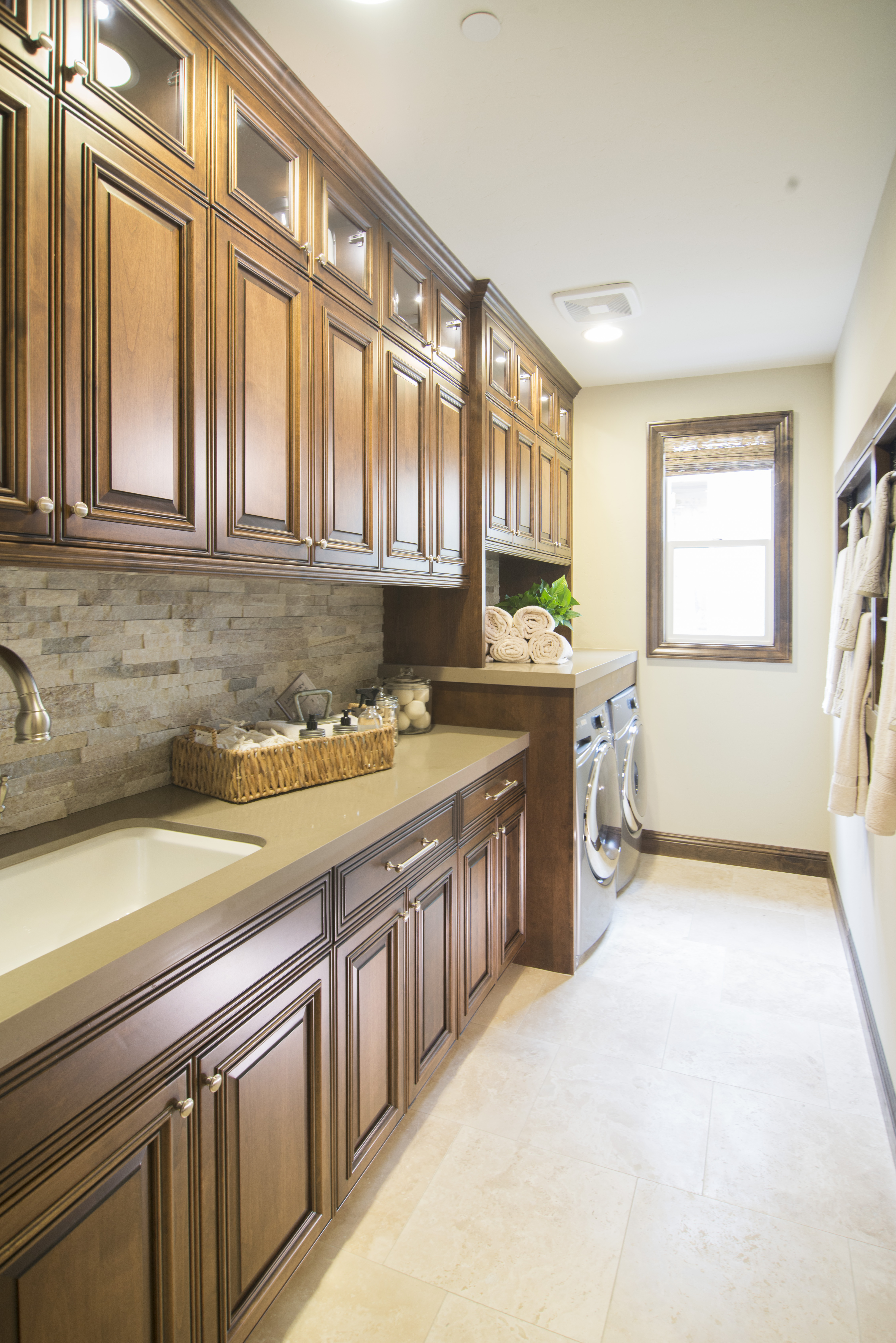 Beautiful Laundry Room Alder Built-Ins with Clear Glass Doors and Puck Lights