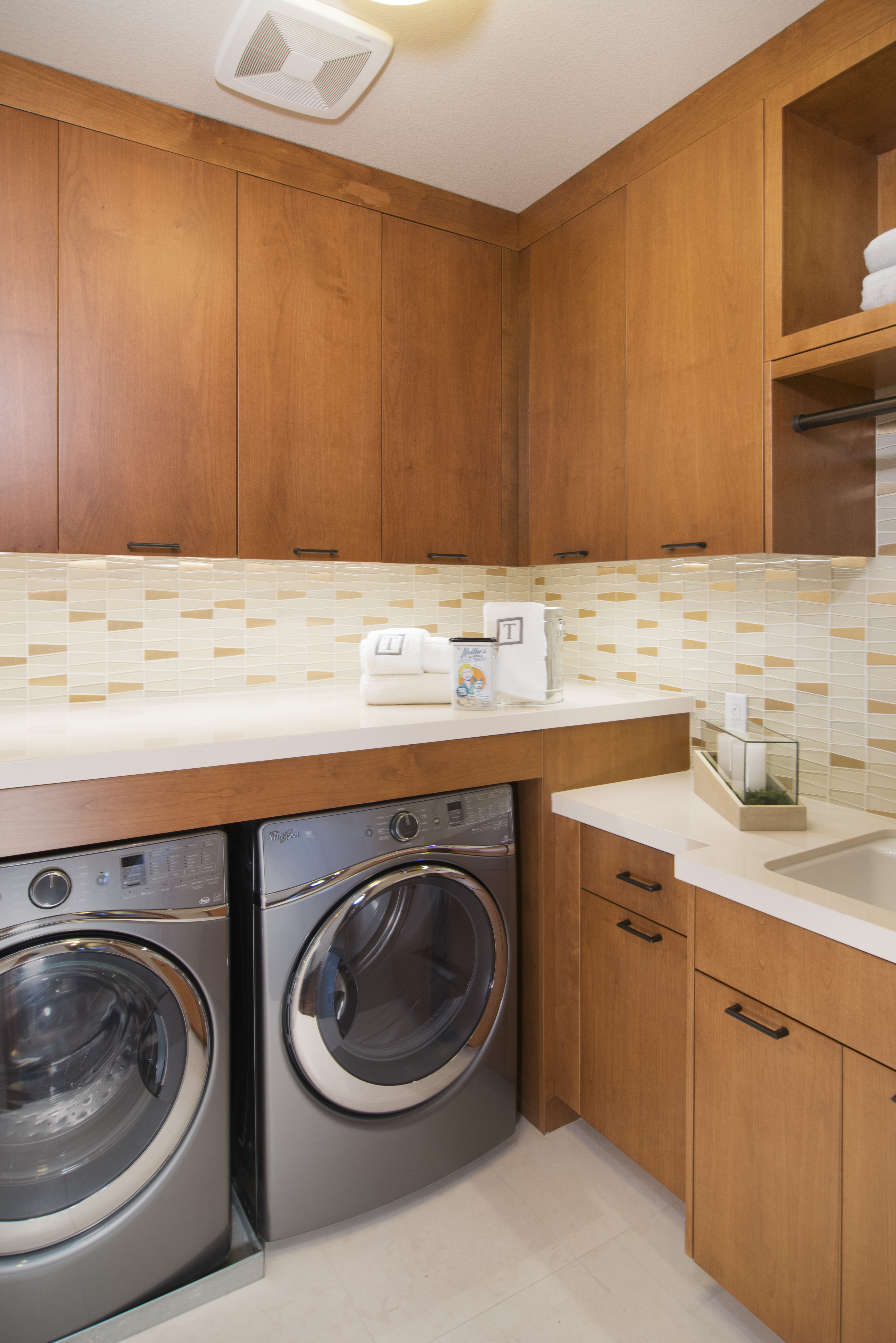 Beautiful Contemporary Laundry Room with a White Counter Top and a Stainless Steel Washer - Dryer