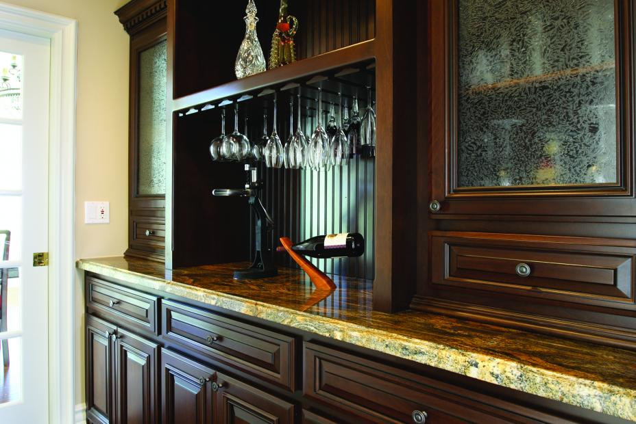 Traditional Chocolate Stained Wine Bar with a Beautiful Granite Countertop, Wine Glass Storage, Glass Doors and Beadboard Backing