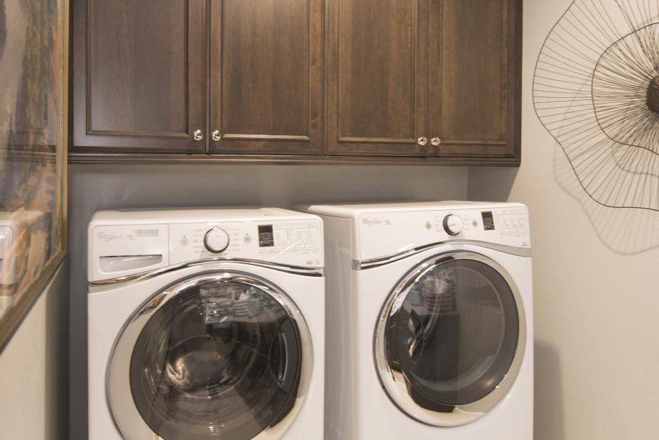 Transitional Laundry Room with Stained Built-Ins, Silver Knobs and White Appliances