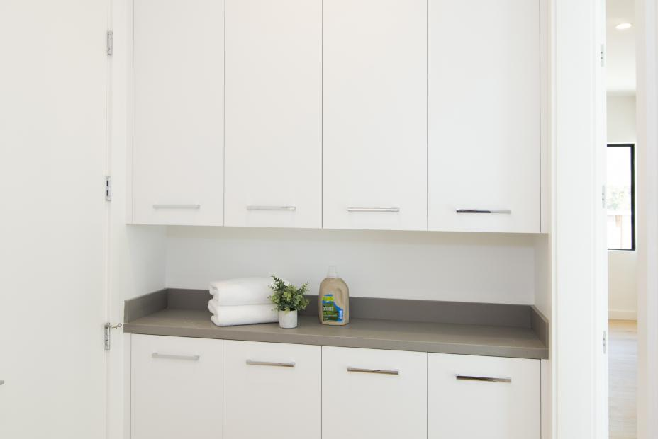 Beautiful white contemporary laundry room with stainless steel pulls