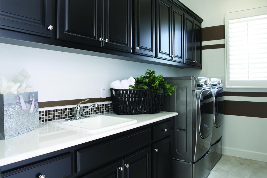 Beautiful Laundry Room Cabinets Stained in a Dark Espresso with White Counter Tops and an LG Washer - Dryer