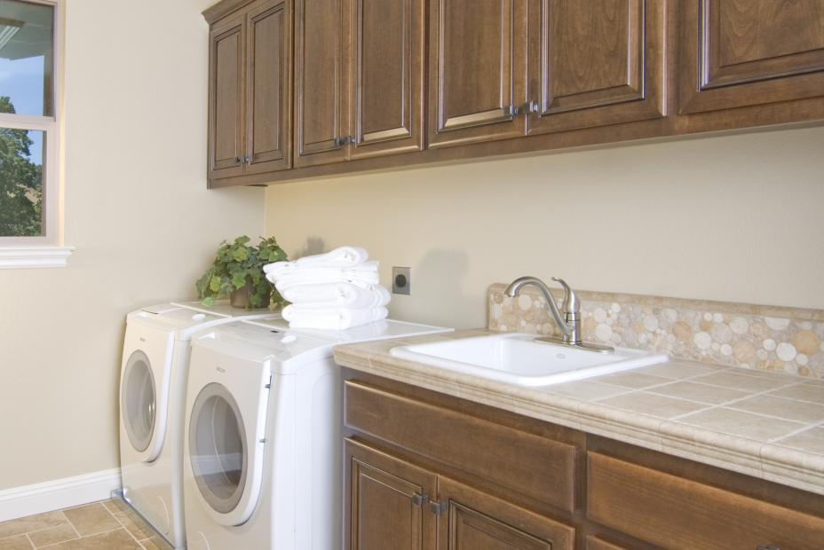 Traditional Stained Laundry Room Cabinets with a Beautiful White Bosch Washer - Dryer