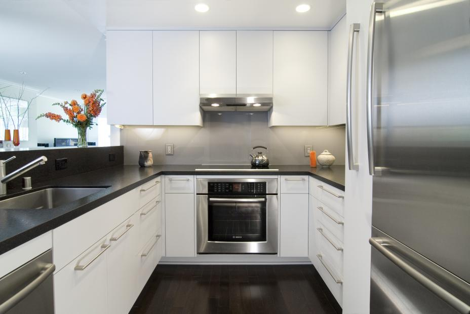 Beautiful Contemporary, White Kitchen Cabinets with Clean Lines, a Dark Countertop and Stainless Steel Appliances