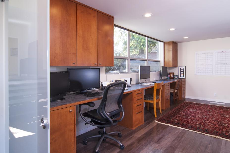 Contemporary Office Built-Ins Finished in a Reddish Stain with a Grey Mixed Counter Top and Silver Hardware