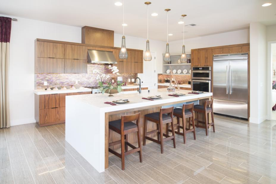 Contemporary Walnut Kitchen with a Beautiful White Waterfall Counter Top and Stainless Steel Appliances