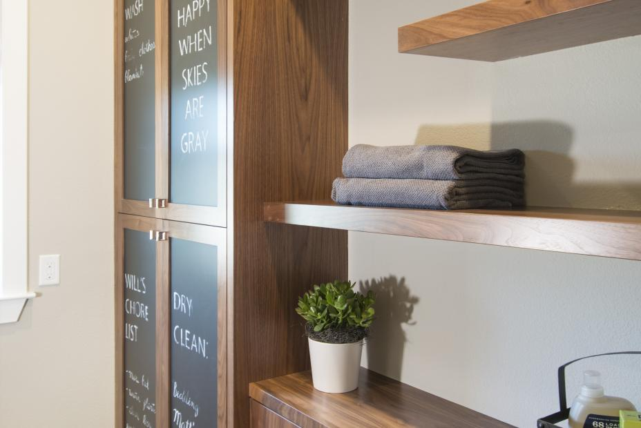 Walnut Contemporary Laundry Room Cabinets with a Built-in Chalkboard, Floating Shelves and Whirlpool Washer - Dryer