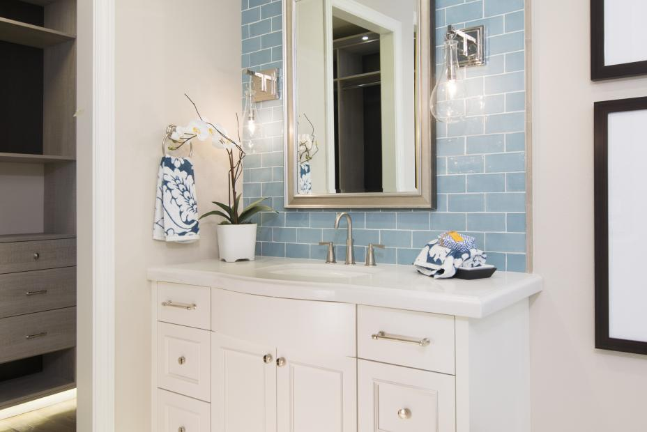 Beautiful White Bathroom Vanity with a White Counter Top, Silver Faucet, Knobs and Pulls