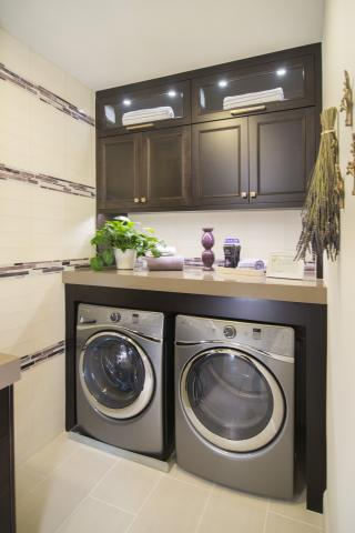 Beautiful Laundry Room Built-In Finished in a Dark Espresso Stain with Glass Doors, Puck Lighting, and a Silver Washer - Dryer