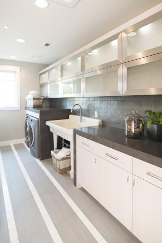Beautiful Contemporary White Laundry Room Cabinets with a Waterfall Counter Top, Aluminum Door Frames and Puck Lights