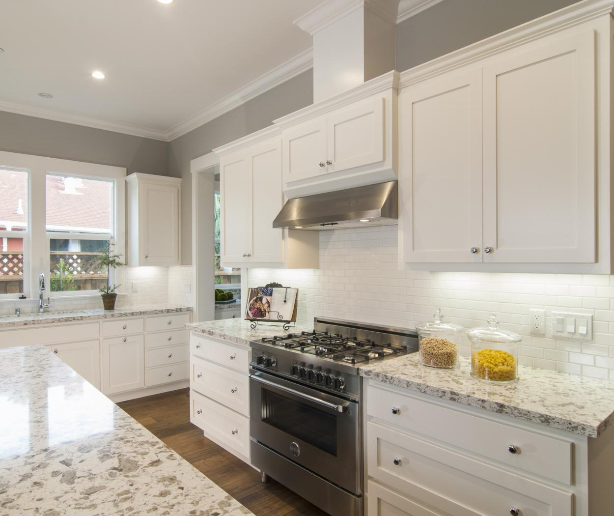 Transitional White, Shaker Style Kitchen with Stainless Steel Appliances and a Beautiful Marble Counter Top