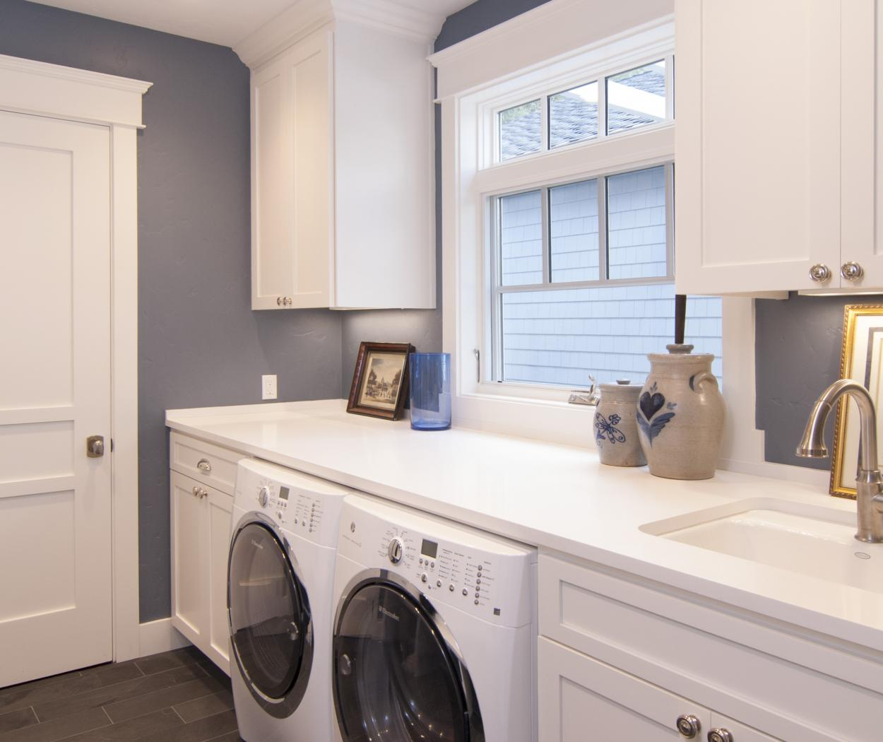White Transitional Laundry Room with Uppers, a White Counter Top and Electrolux Washer - Dryer