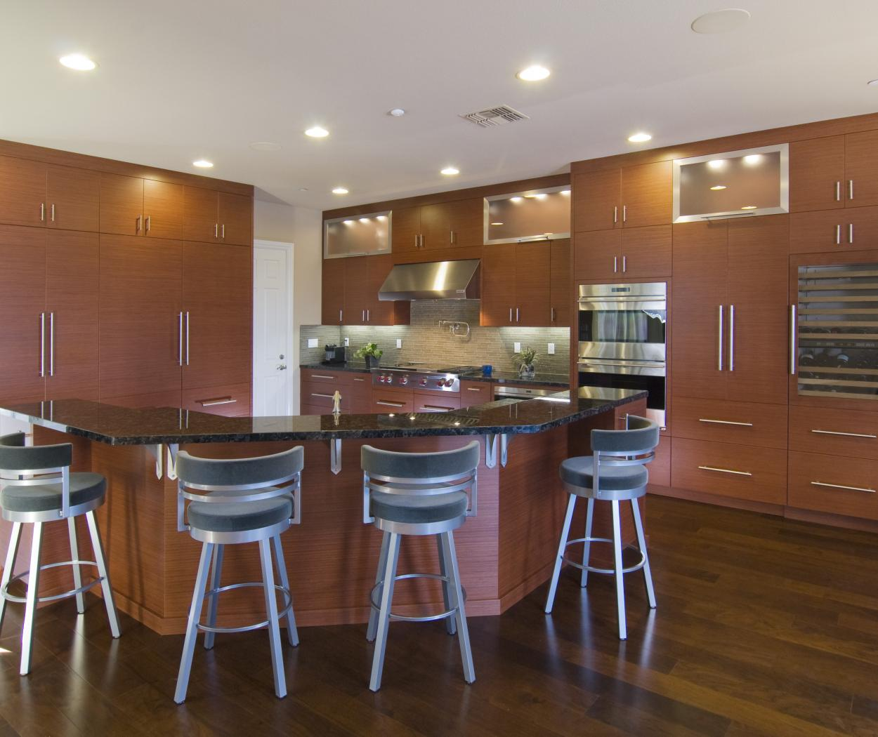 Contemporary Kitchen with a Beautiful Island, Dark Counter Tops, Aluminum Door Frames, Puck Lighting and Stainless Steel Appliances