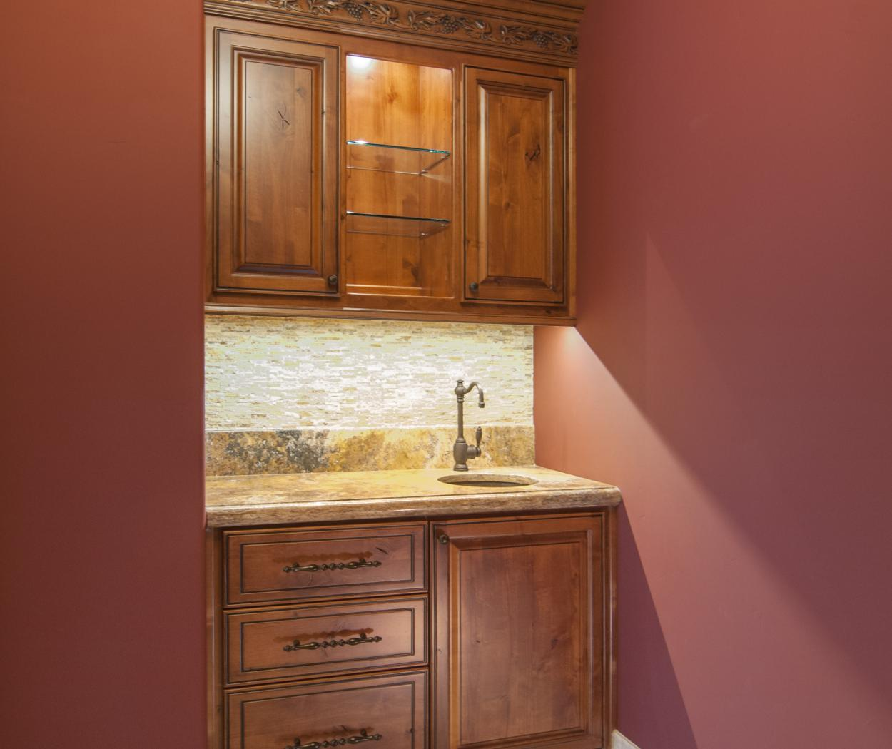 Traditional Knotty Alder Built-In with a Beautiful Oil Rubbed Bronze Faucet, Granite Counter Top and Glass Shelves