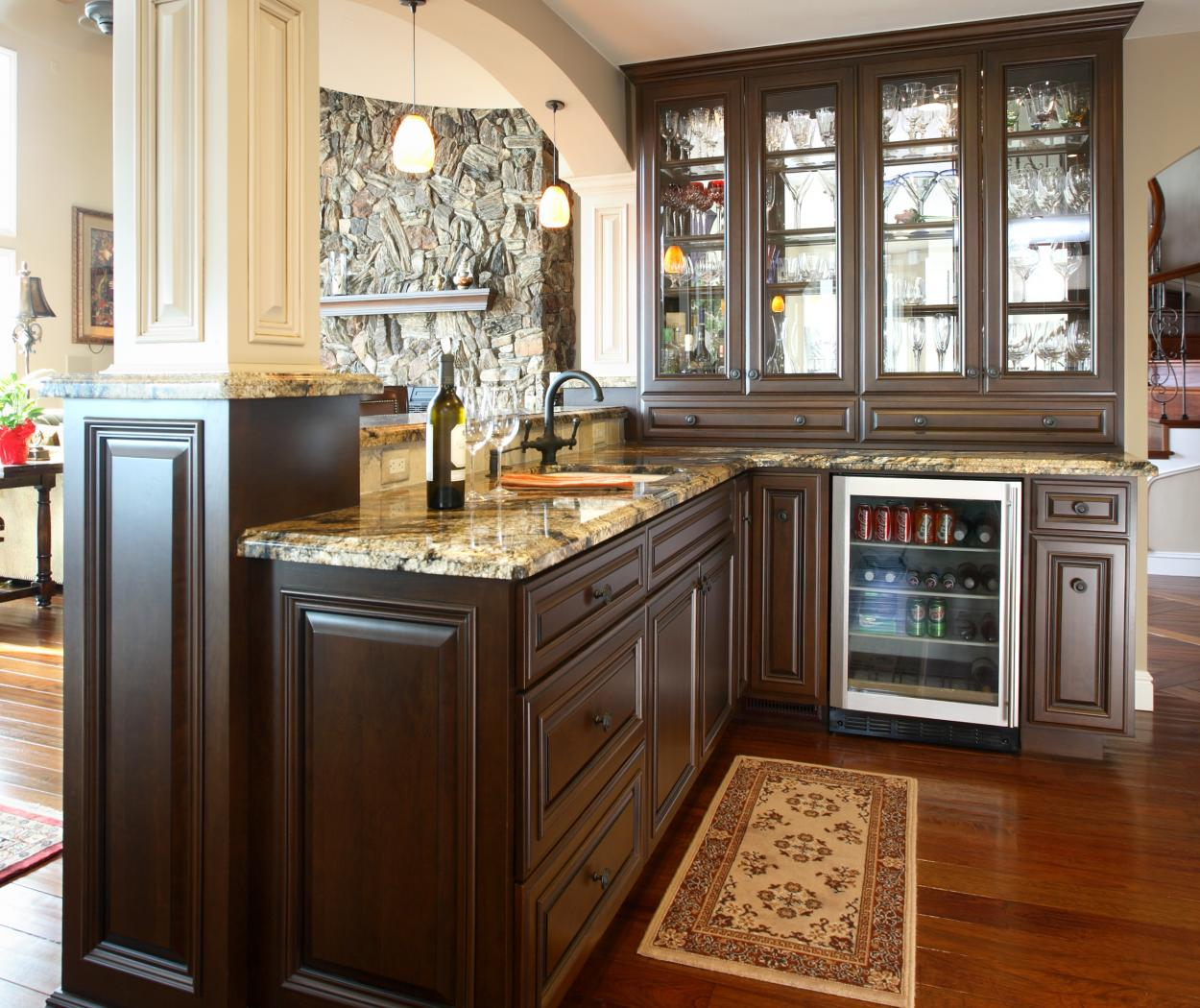 Traditional Chocolate Stained Wet Bar with a Beautiful Granite Countertop, Glass Doors and Oil Rubbed Bronze Hardware