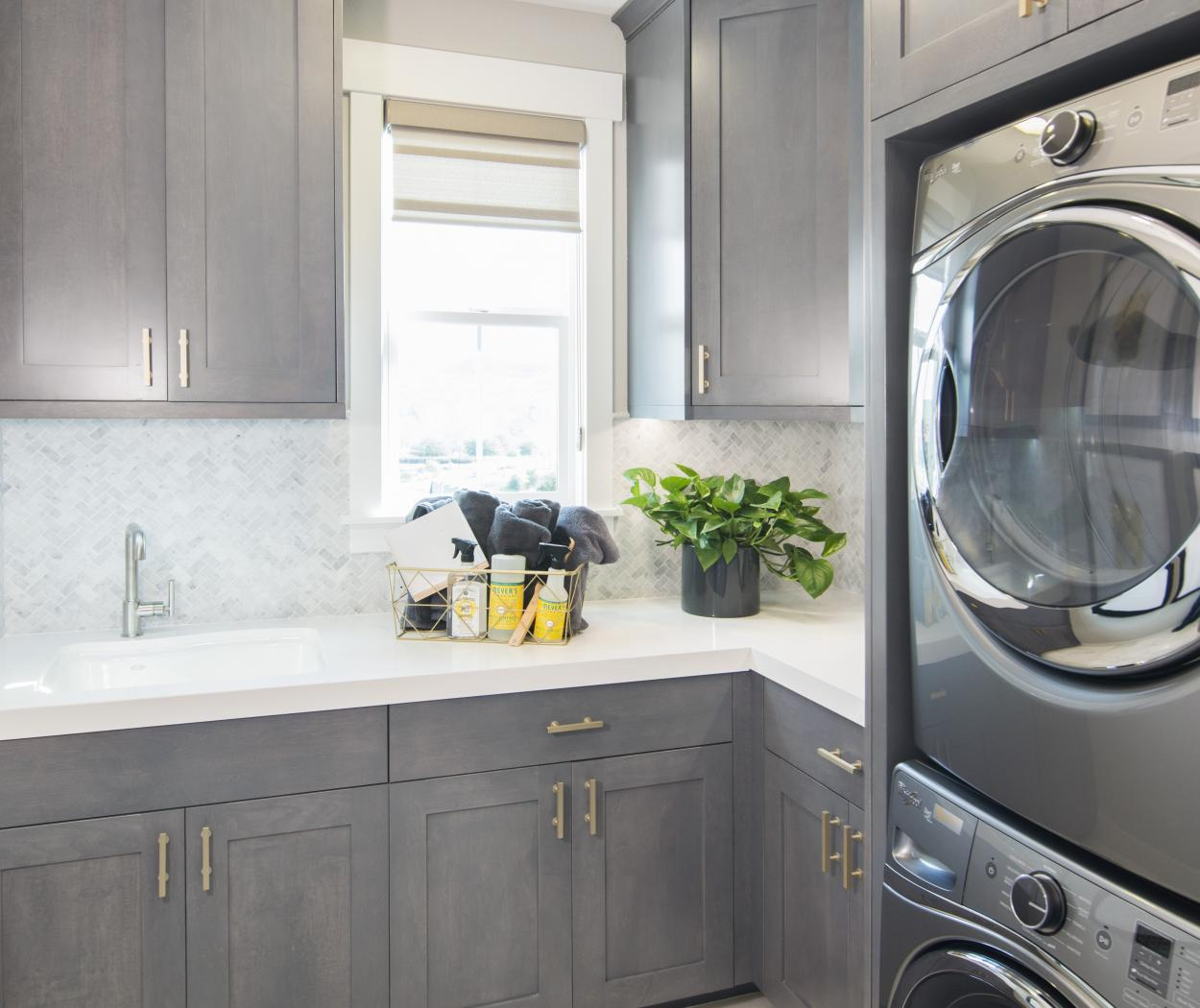 Beautiful Laundry Room, Shaker Style with a White Counter Top, Gold Pulls and Dark Silver Washer - Dryer