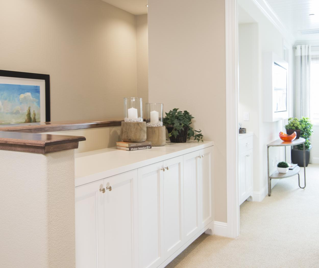 Beautiful Super White Hallway Built-In with Silver Knobs and a White Counter Top
