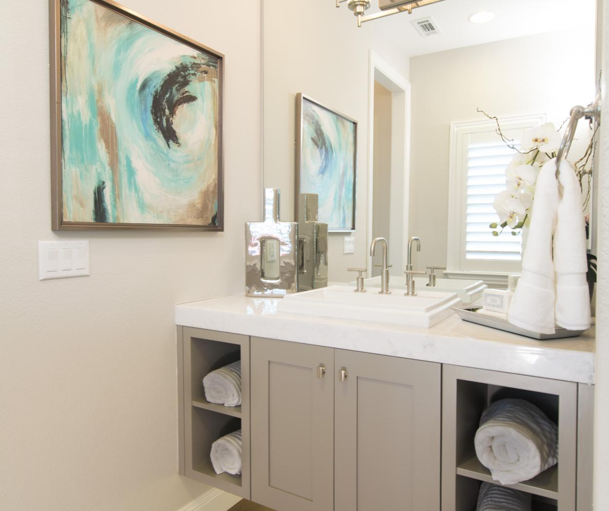 Beautiful Painted Beige, Shaker Style Bathroom Vanity with Open Shelves, a White Counter Top and a Silver Faucet