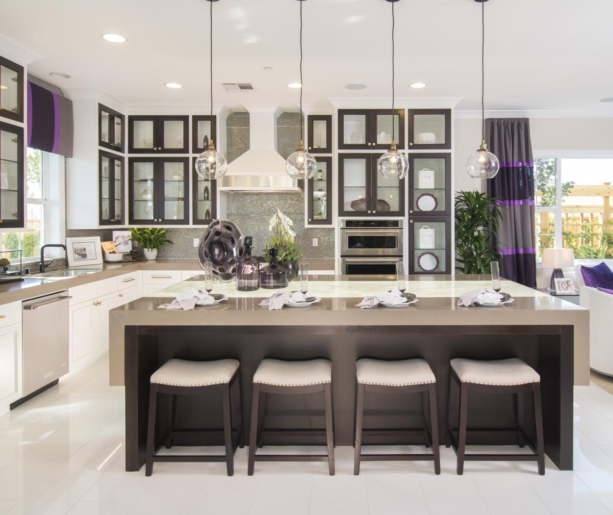 Beautiful White Kitchen with Espresso Stained Door Frames, Glass Doors, Waterfall Island and Gold Knobs - Pulls