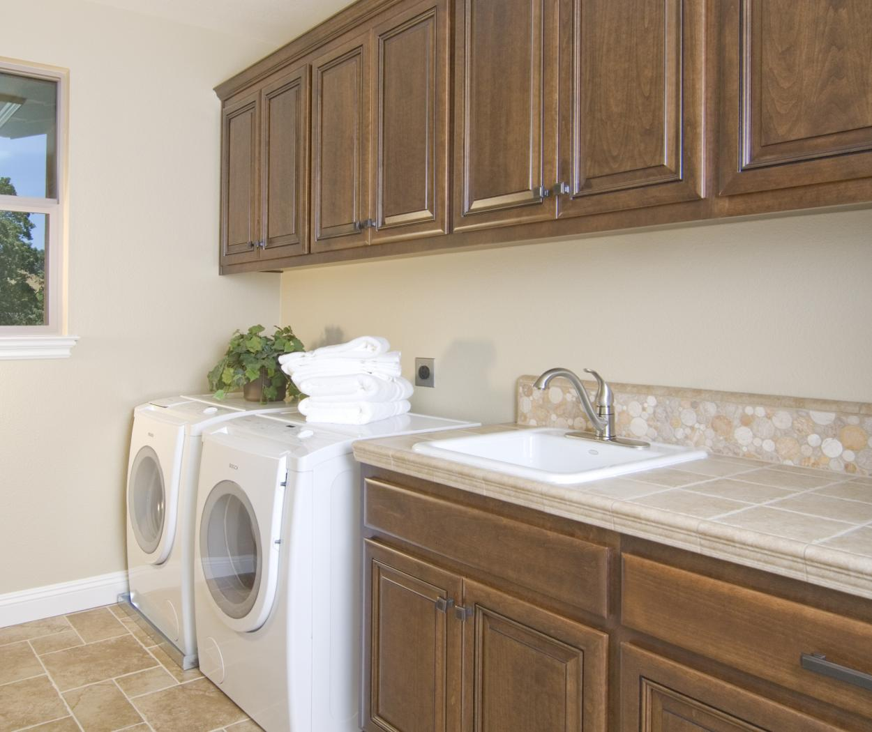 Traditional Stained Laundry Room Cabinets With A Beautiful White Bosch  Washer   Dryer