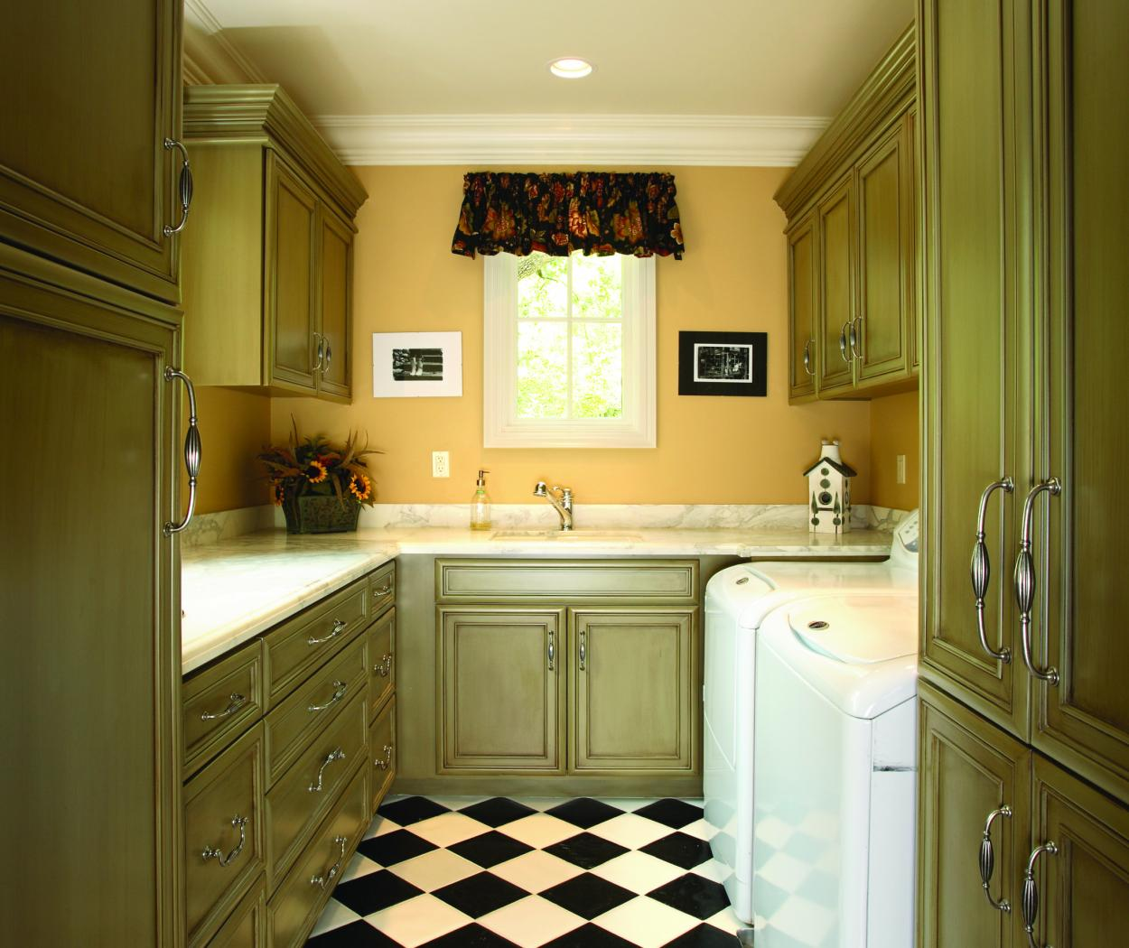 Transitional Green Laundry Room Cabinets with a Beautiful Marble Countertop, Decorative Hardware and Checkered Floors