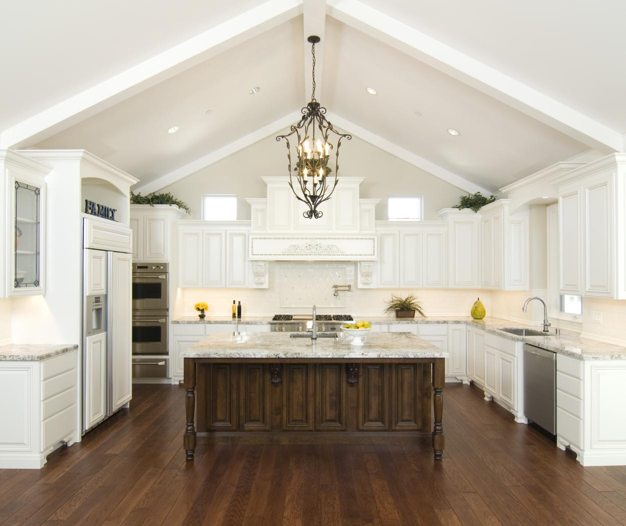 Traditional White Kitchen with a Chocolate Stained Island, Beautiful Marble Countertops and Stainless Steel Appliances