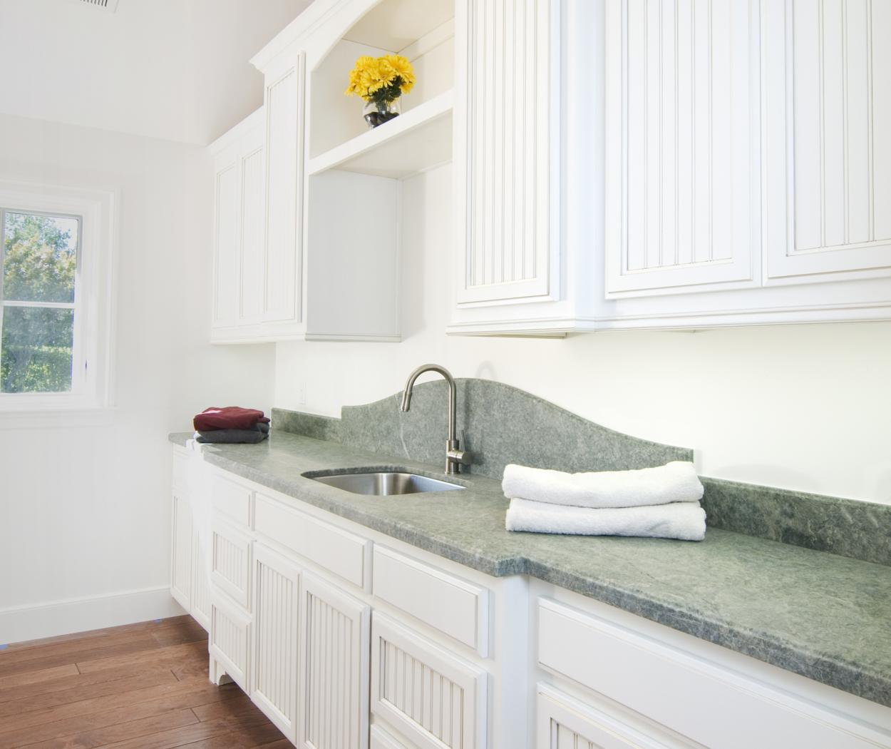 Beautiful White Beadboard Laundry Room Cabinets with an Open Arched Rail and Dark Grey Mixed Countertop