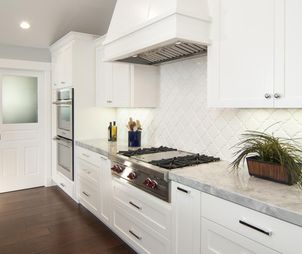 White Transitional, Shaker Style Kitchen with Beautiful Marble Countertops and Stainless Steel Appliances