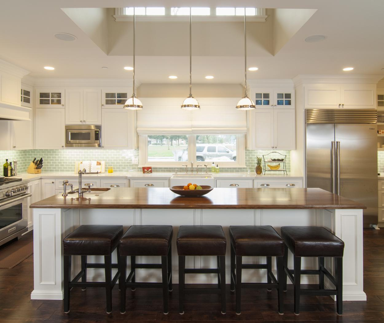 Transitional White Kitchen with a Long Matching Island, Walnut Counter Top, Glass Doors and Stainless Steel Appliances