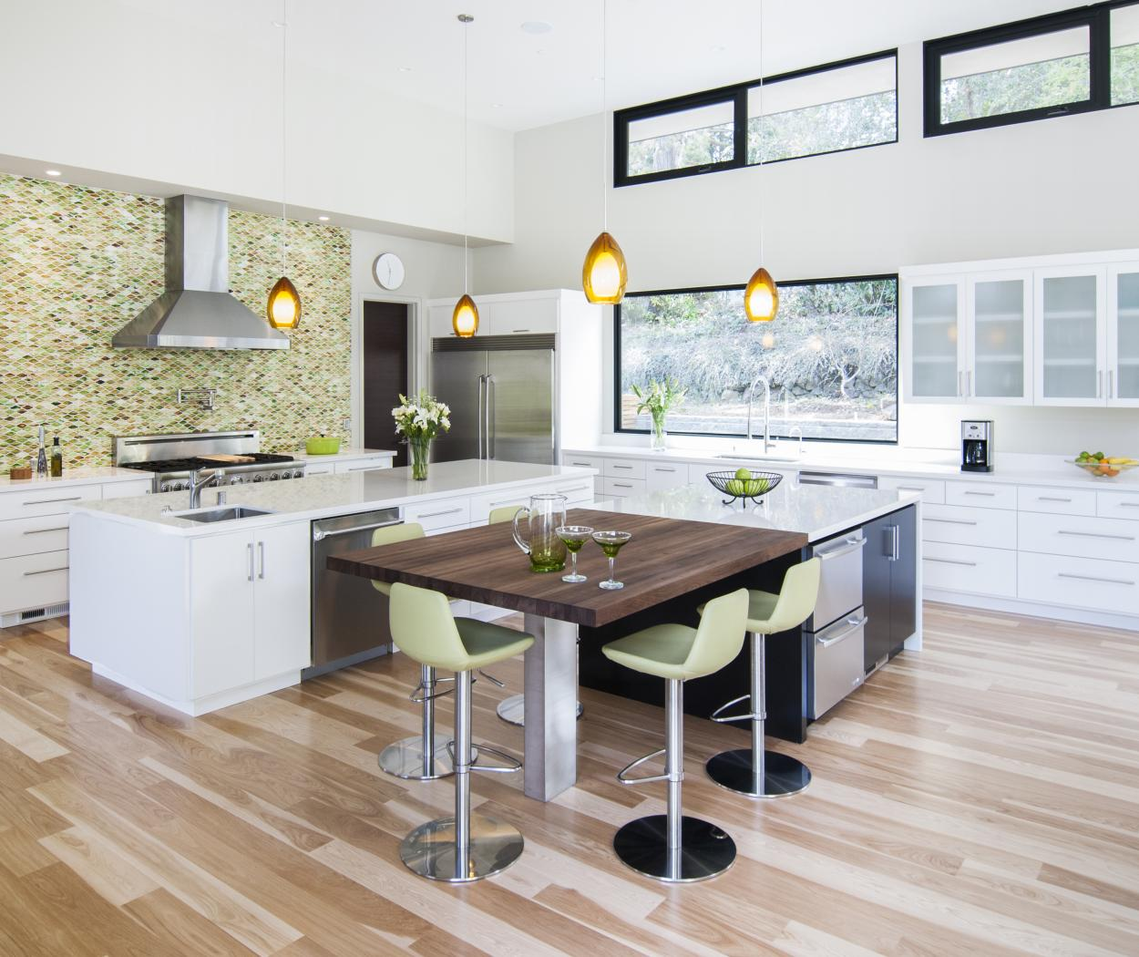 White Contemporary Kitchen with a Beautiful Green Mixed Back Splash, White Counter Tops, Silver Hardware and Stainless Steel Appliances