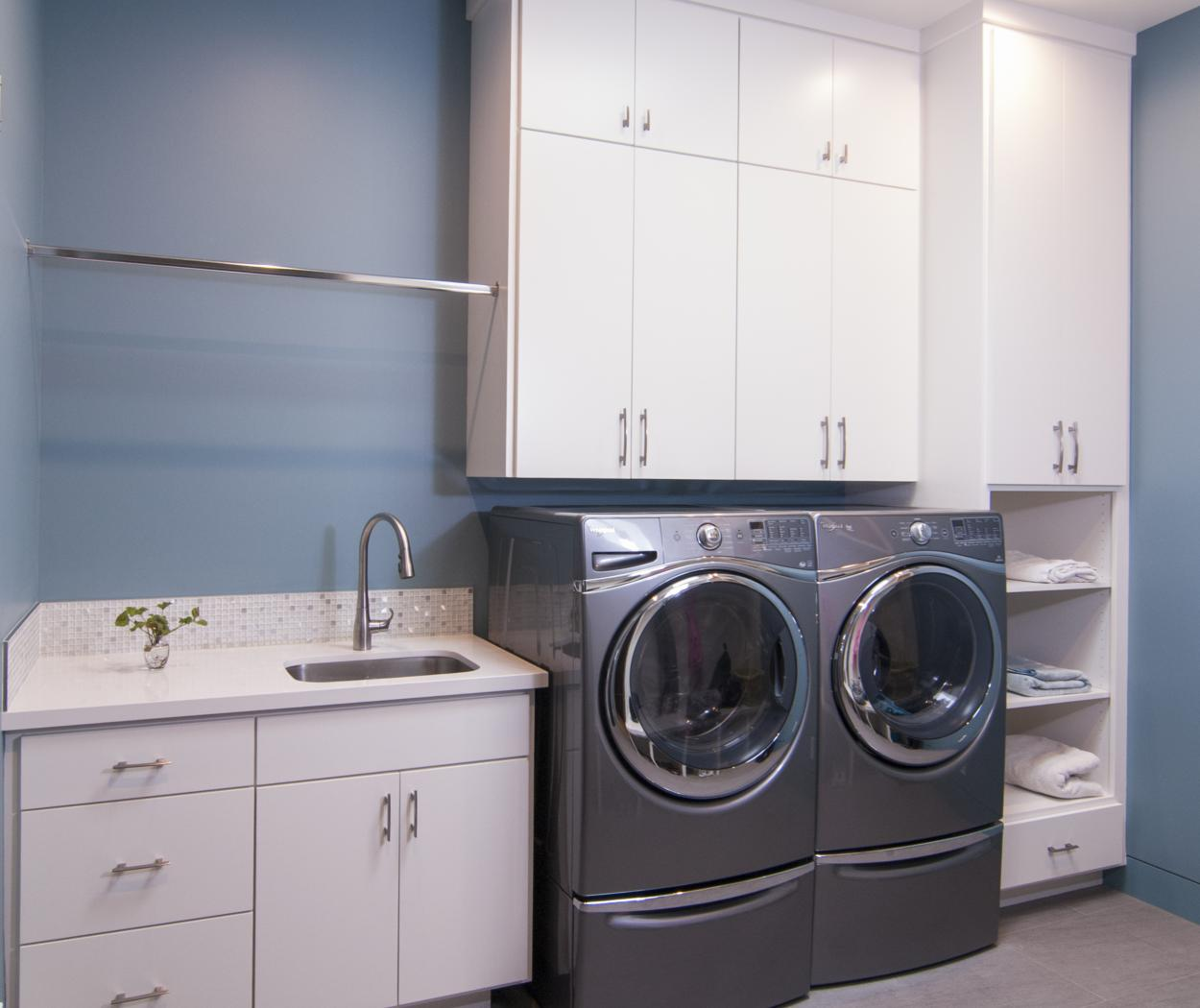 Contemporary White Laundry Room Cabinets with Open Cubbies and a Whirlpool Washer - Dryer