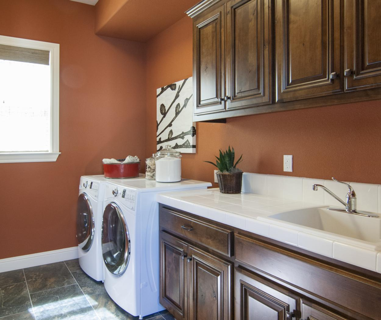 Beautiful Traditional, Knotty Alder Laundry Room Cabinets with a White Counter Top and White Appliances