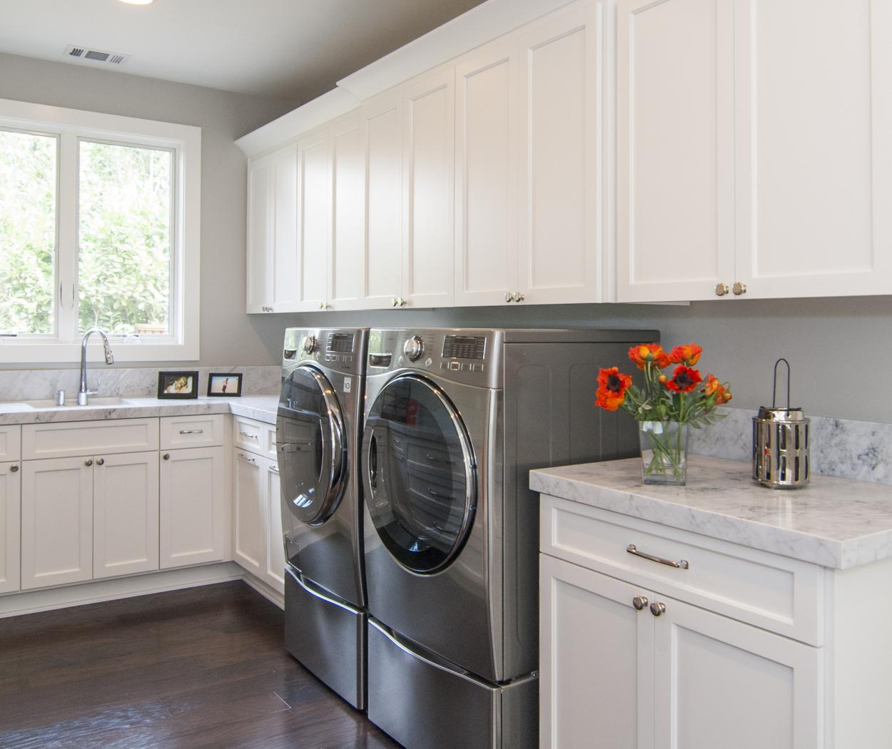 Beautiful Transitional White Laundry Room Cabinets with Marble Counter Tops and an LG Washer - Dryer