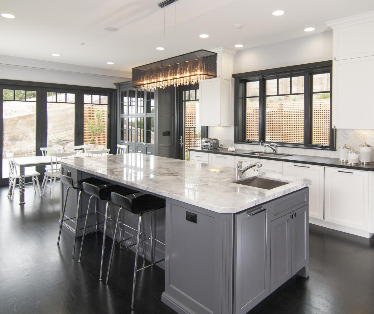 Transitional White Kitchen with a Beautiful Grey Island, Marble Counter Tops, Glass Doors and Silver Hardware