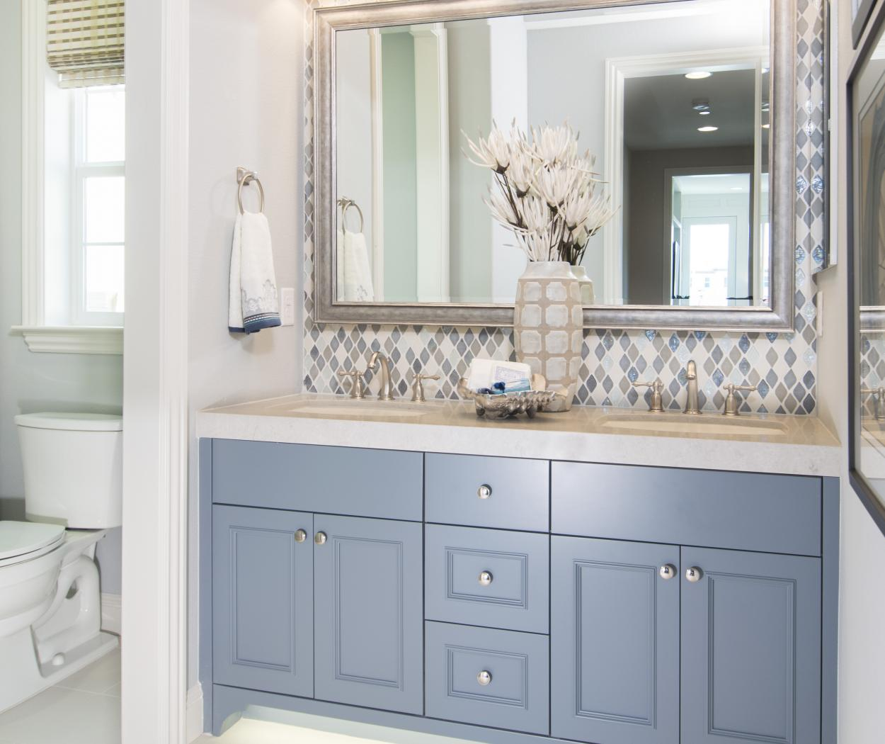 Light Blue Master Bathroom Cabinets with Double Sinks and Silver Knobs