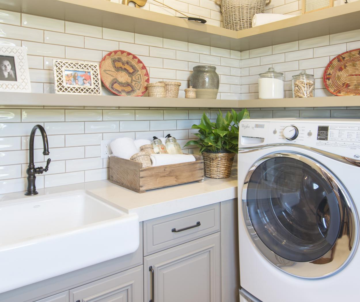 Traditional Painted Laundry Room Cabinets with a Farm House Sink, Oil Rubbed Bronze Faucet, Floating Shelves and Whirlpool Washer - Dryer